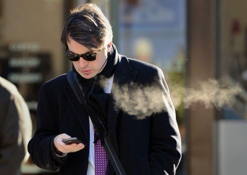 Žmogus su išmaniuoju telefonu gatvėje