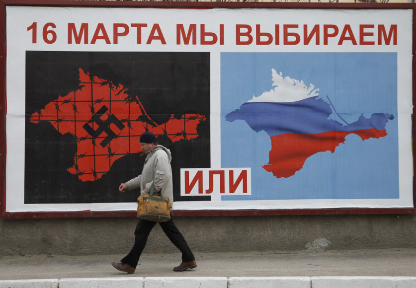 A man walks past a poster calling people to vote in a referendum in the Crimean city of Sevastopol March 16, 2014. Residents of the Crimean penisular prepared to vote in a referendum on Sunday that is widely expected to transfer control of the Black Sea region from Ukraine to Moscow, despite an outc