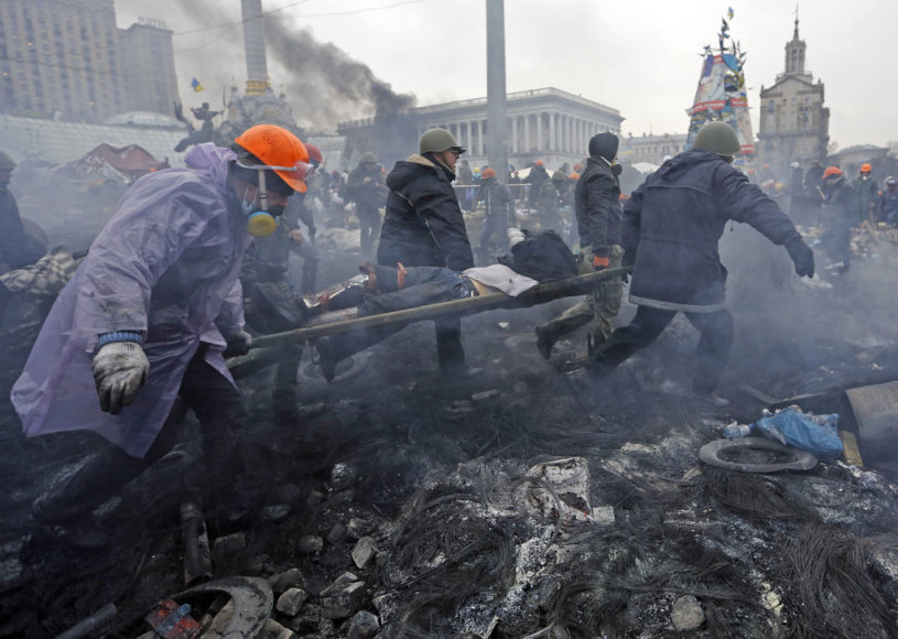 """Anti-government protesters carry an injured man on a stretcher after clashes with riot police in the Independence Square in Kiev February 20, 2014. Ukrainian protesters hurling petrol bombs and paving stones drove riot police from the central square in Kiev on Thursday despite a """"truce"""" which embatt"""