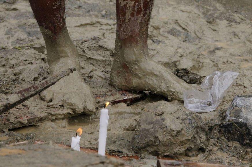 Dega žvakės pagerbti žuvusiems per žemės nuošliaužą.
