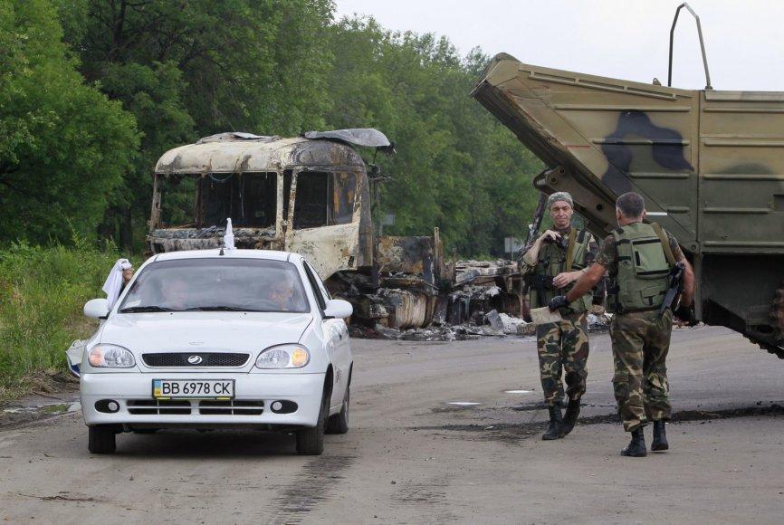 Vyrai su baltais skudurėliais atomobiliu važiuoja pro separatistų patikrinimo postą Luhanske
