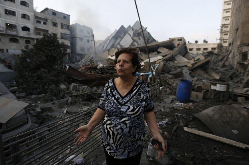 Gazos Ruože moteris prie pastato griuvėsių