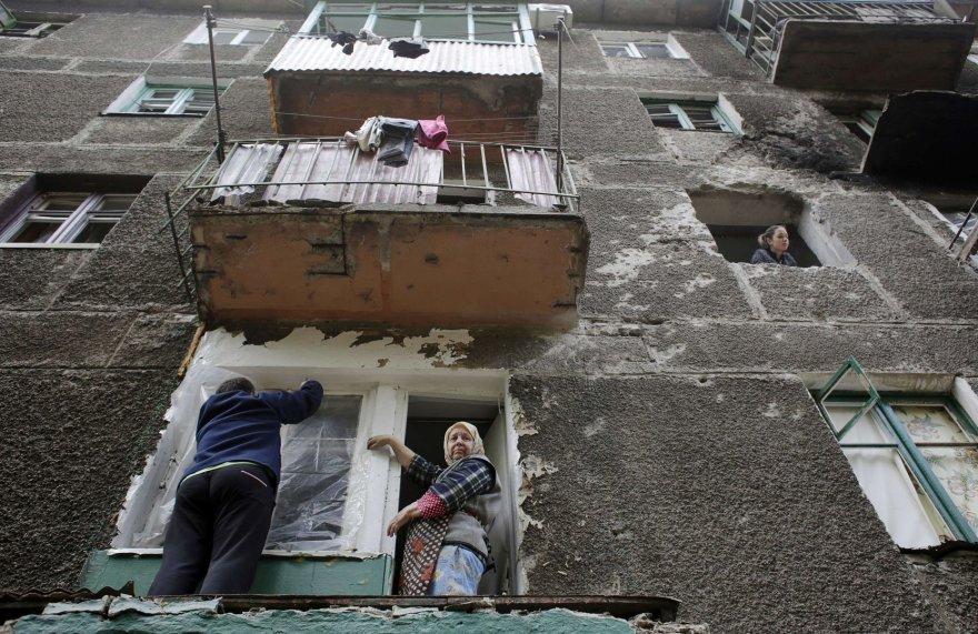 Apšaudyto daugiabučio gyventojai tvarko išdužusius langus.