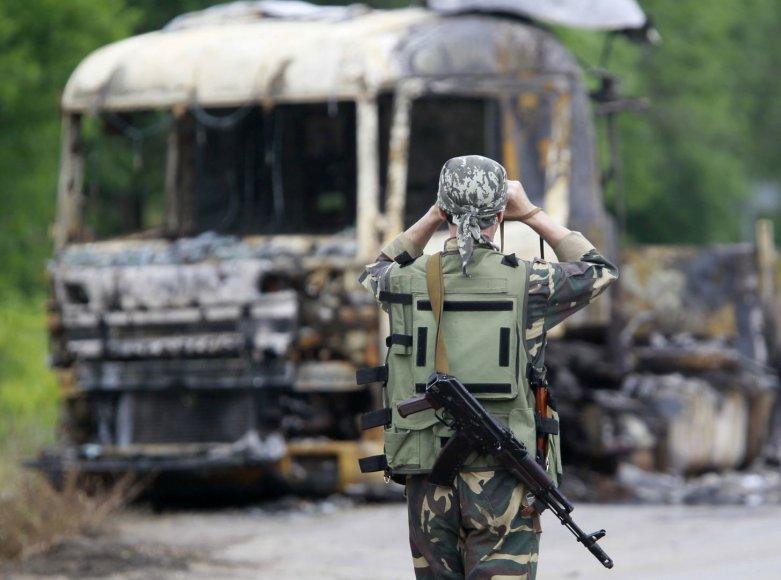 Rusų teroristas netoli sudeginto vilkiko, prie patikrinimo posto Luhanske