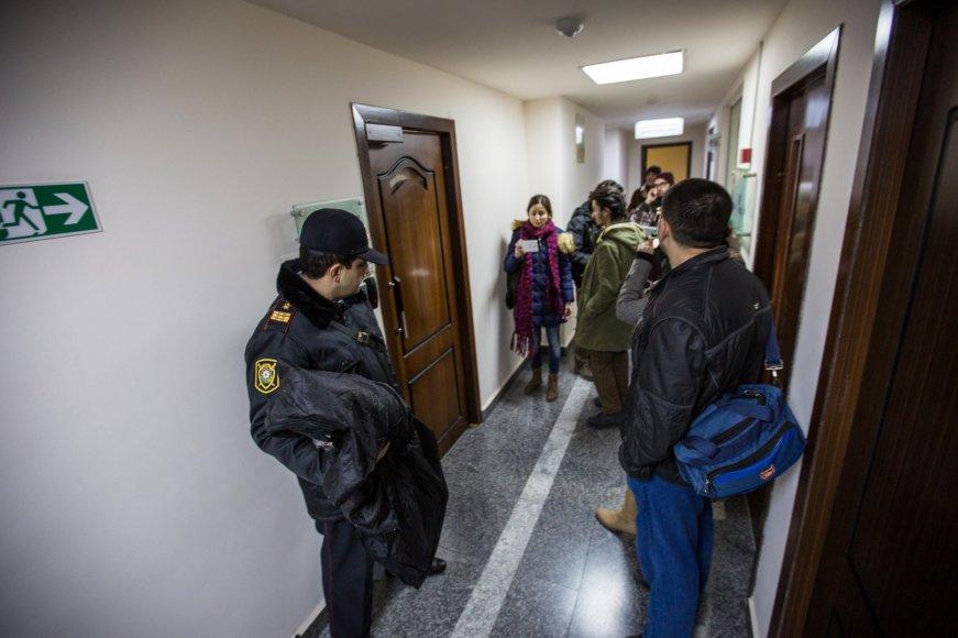 """Policininkas """"Laisvosios Europos"""" radijo pastato koridoriuje su žurnalistais"""