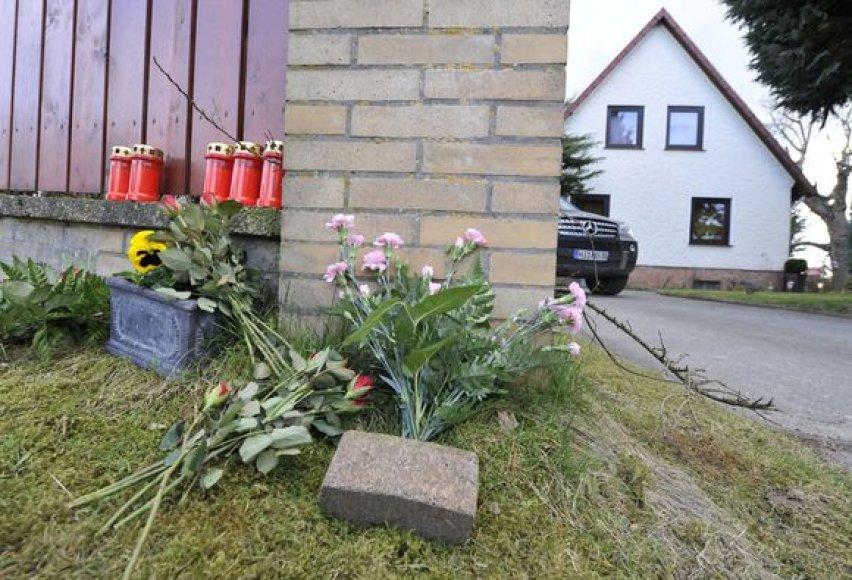 Gėlės ir žvakės padėtos šalia namo.