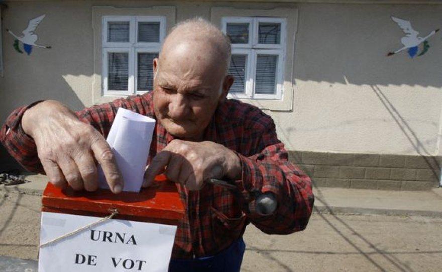 Senukas meta rinkimų lapelį į mobilią balsavimo dėžutę.