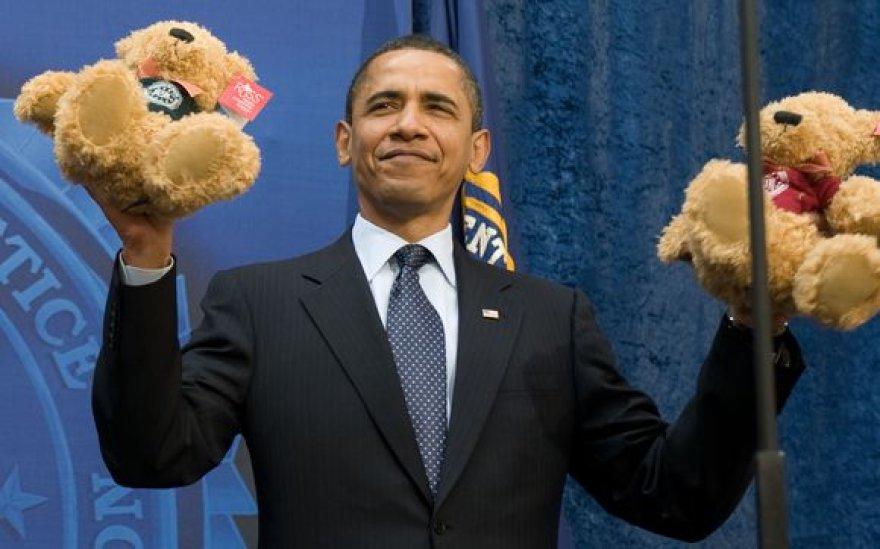 Barackas Obama laiko pliušinius meškiukus.