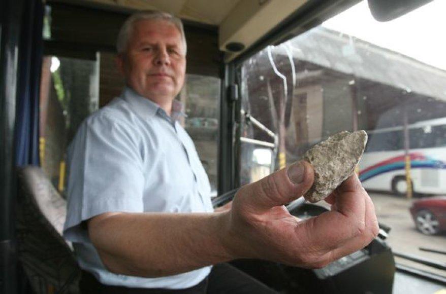 Vairuotojas demonstruoja akmenį, su kuriuo buvo išdaužtas langas.