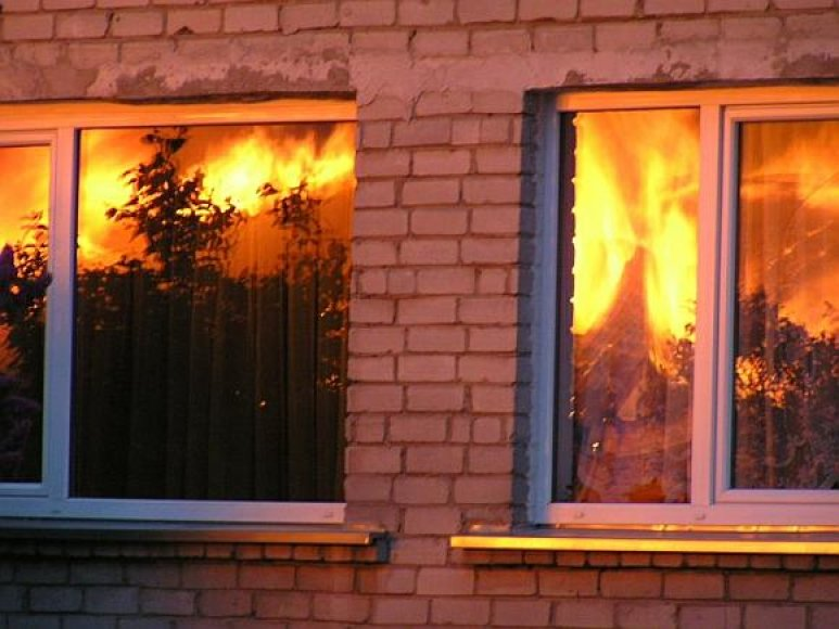 Liepsnos atspindžiai gretimų namų languose.