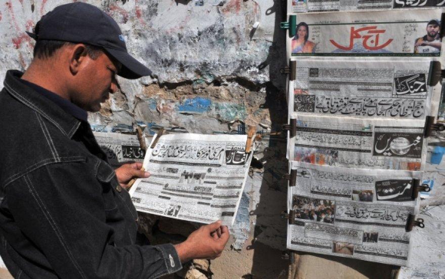Pakistanietis skaito laikraštį urdu kalba, kuriame pranešama apie Abdulo Ghani Baradaro suėmimą.