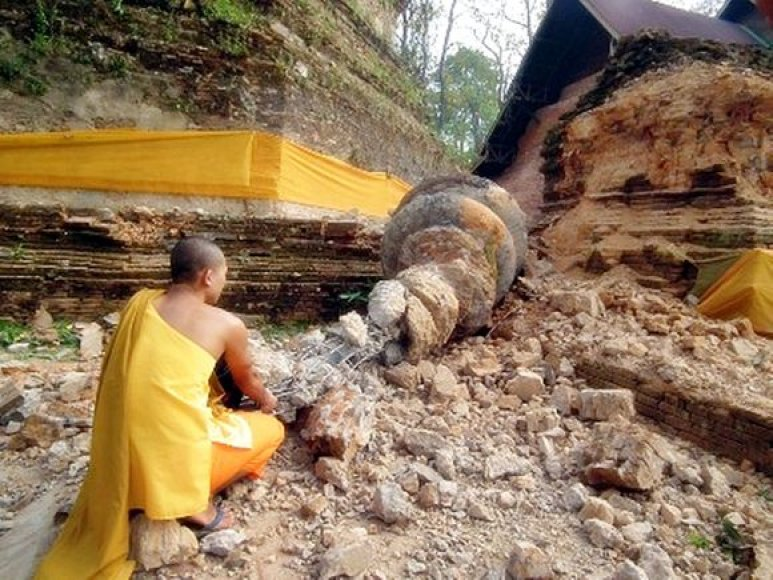 Mianmaro pasienyje Tailando budistų vienuolis sėdi prie sugriautos šventyklos.