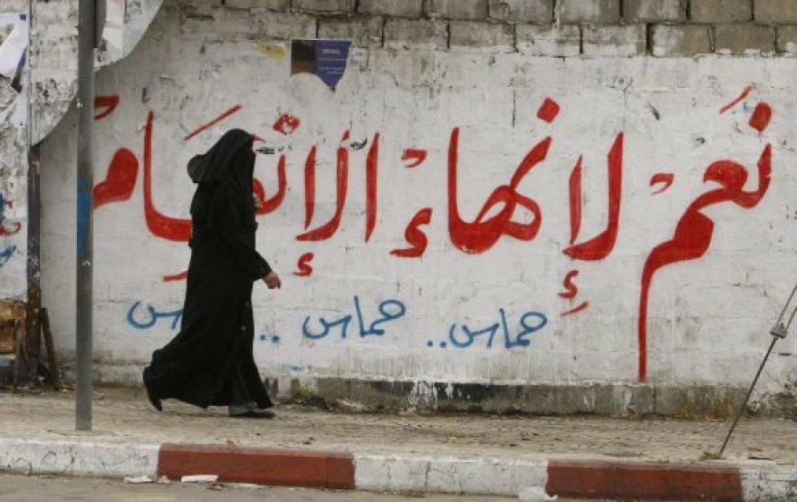 """Palestinietė Gazos mieste eina pro užrašą ant sienos """"Taip pasidalijimo pabaigai""""."""