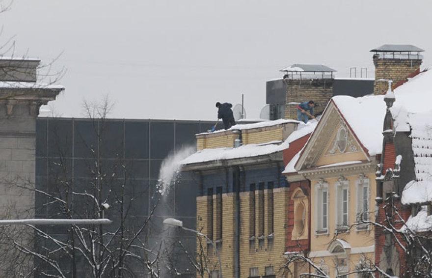 Du vyrai nuo stogo kasa sniegą