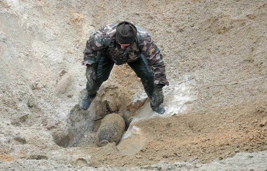 Išminuotojas 50 kg aviacinę bombą ruošia sunaikinimui buvusiame Rūdninkų poligone. Pavojingų sprogmenų čia aptinkama nuolat.