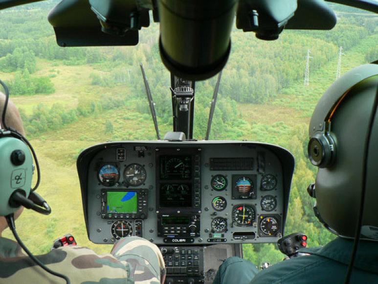 Pasieniečių sraigtasparnis skrenda virš miško
