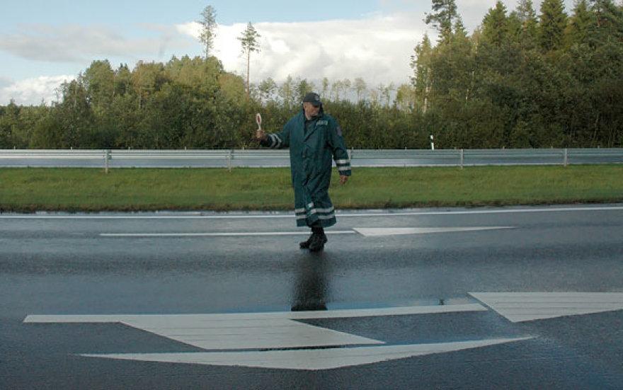 Policininkas įvykio vietoje reguliuoja eismą