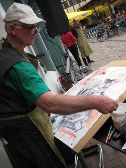 Menininkas lieja akvarelę.