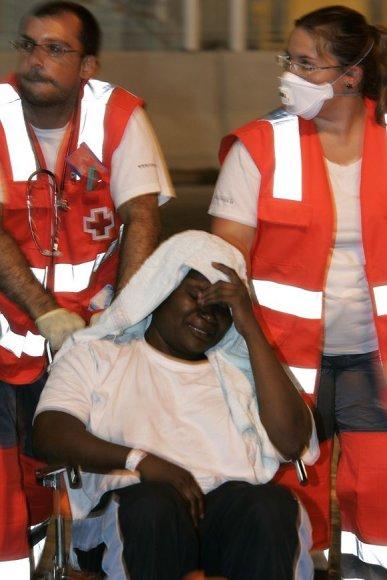 Raudonojo Kryžiaus darbuotojai suteikia pagalbą vienam iš pabėgėlių.