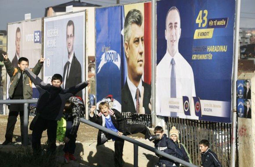 Vaikai pozuoja prie Kosove vykstančių rinkimų plakatų.