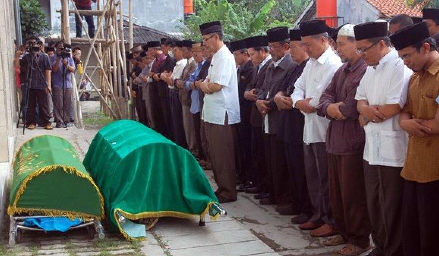 Laidotuvių akimirka. Musulmonų minia nužudė tris vieno negausaus islamo judėjimo narius.