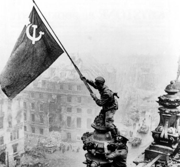 Garsioji nuotrauka, kaip rusų kareiviai kelia ant Reichstago sovietų vėliavą.