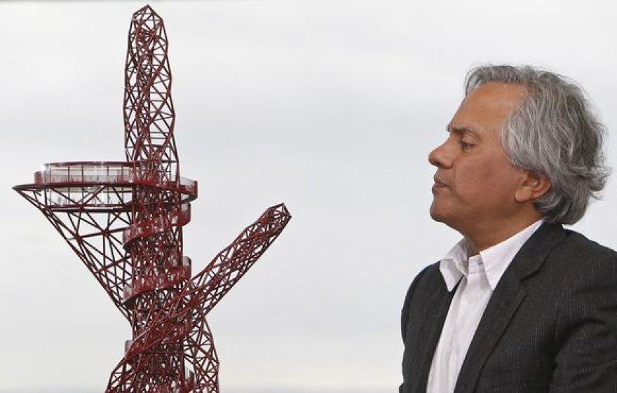 Skulptorius Anishas Kapooras ir jo suprojektuoto statinio maketas
