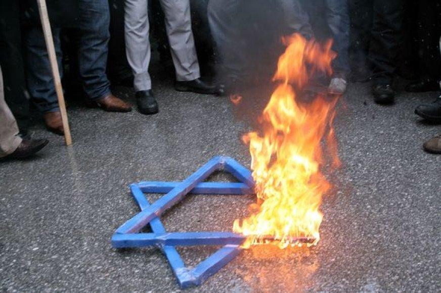 Demonstrantai priešais Izraelio amabasadą Ankaroje (Turkija) degina Dovydo žvaigždę, smerkdami Izraelio atakas Gazoje.
