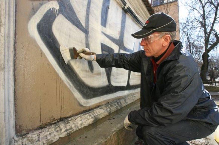Pastatų sienas nuo grafitų šveičiantys valytojai sako sulaukiantys praeivių priekaištų dėl besitaškančio vandens.