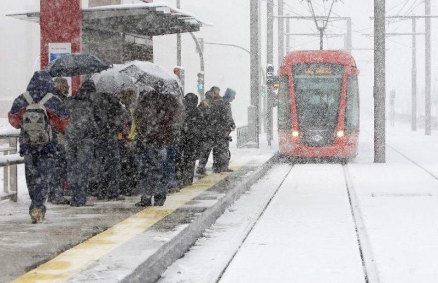 Žmonės, pasislėpę po skėčiais, laukia tramvajaus.