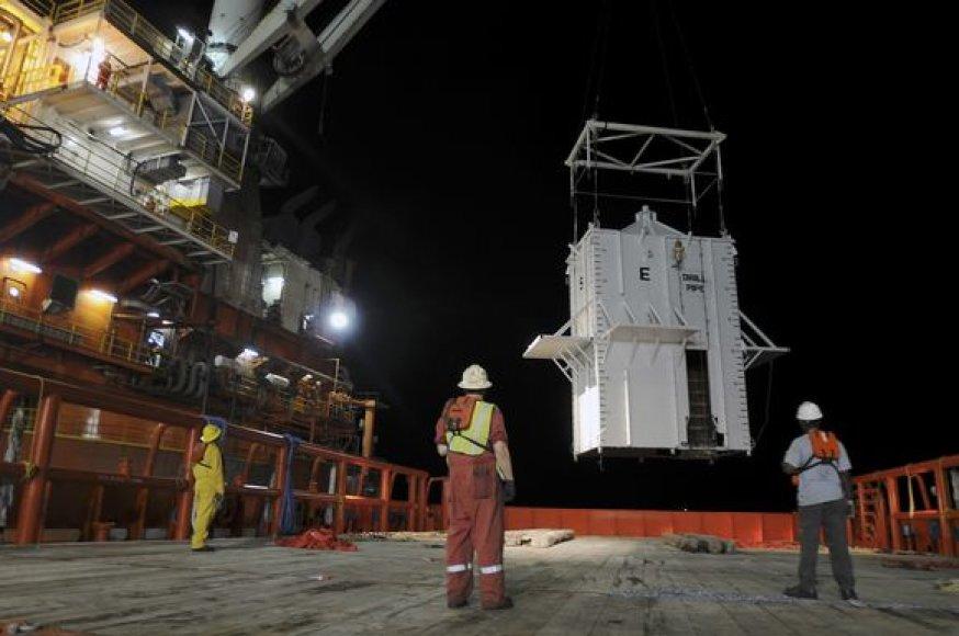 Meksikos įlankoje naftą sulaikantis gaubtas pakabintas virš pramušto gręžinio.