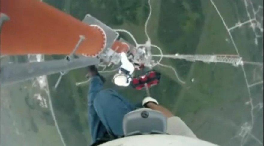 Radijo antenų remontininkas lipa į bokštą.