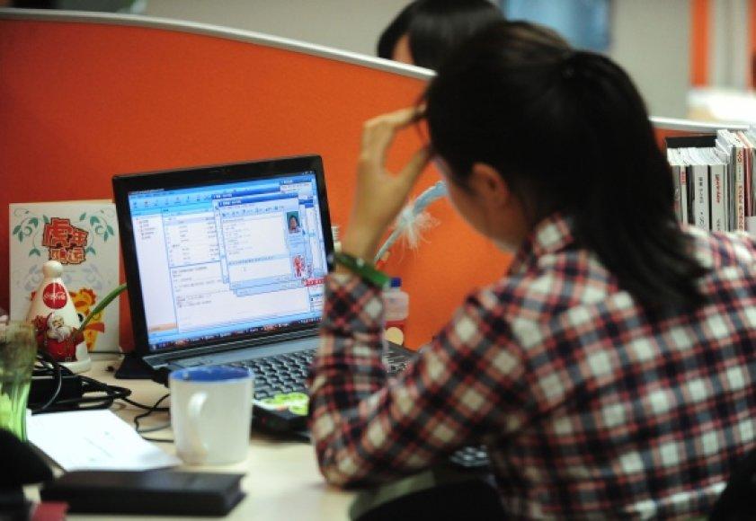 Mergina dirba su kompiuteriu.