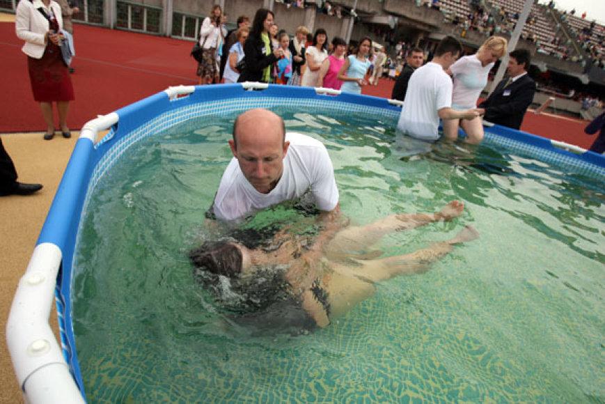 Jehovos liudytojais norintys tapti žmonės krikštijami ne apšlakstant vandeniu, bet akimirkai panardinami vandenyje.