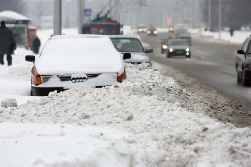 Šalikelėse palikti automobiliai trukdo kelininkams nuvalyti apsnigtas gatves.