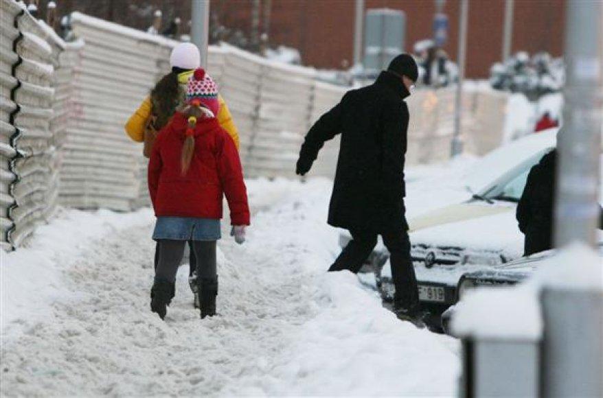 Dalis praeivių, neįveikę storo sniego sluoksnio, kelionę tęsia judraus Karaliaus Mindaugo prospekto važiuojamąja dalimi.