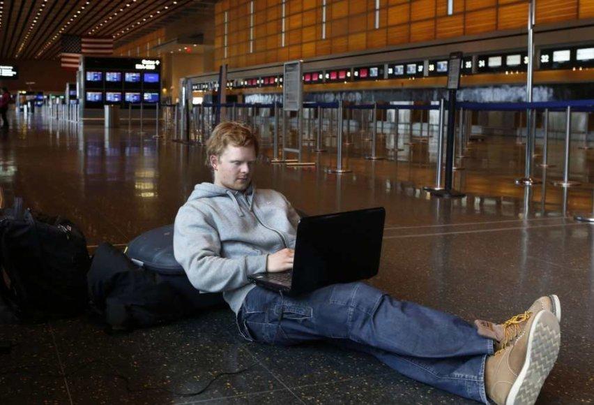 Žmogus dirba su kompiuteriu oro uoste