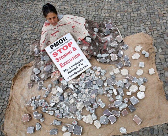 Moteris protestuoja prieš užmėtymą akmenimis