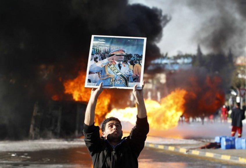 Protestuotojai laiko Muamaro Kadhafi portretą netoli degančio benzinvežio.