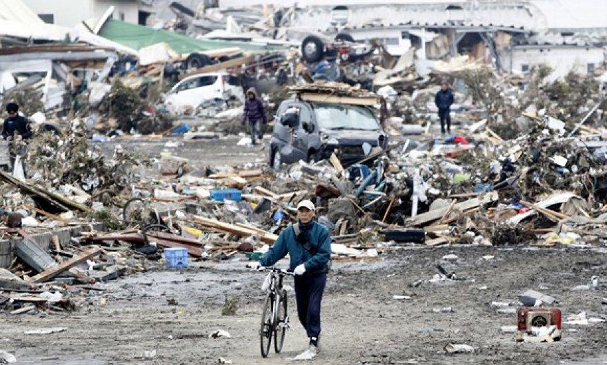Tarp nuolaužų vaikštantys žmonės Sendajaus mieste.