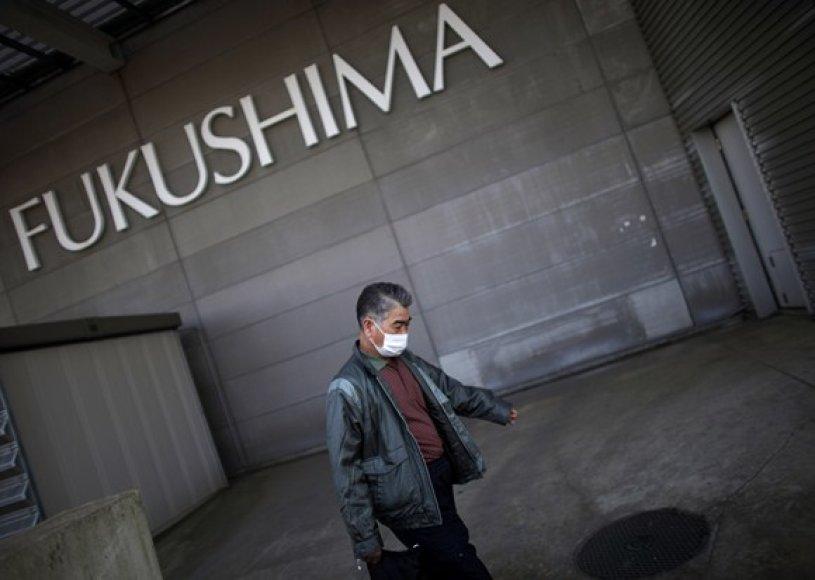 Vyras eina į Fukušimos evakuacijos centrą.