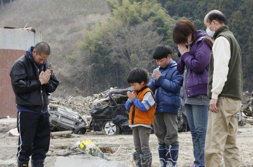 Šeima padėjo gelių ir meldžiasi šalia savo buvusių namų.
