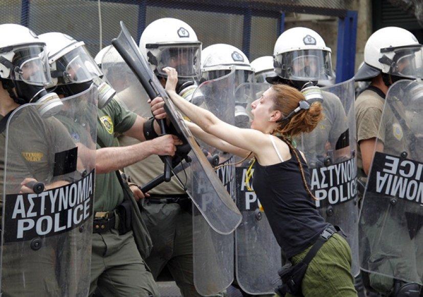 Protestuotoja puola riaušių policininką.