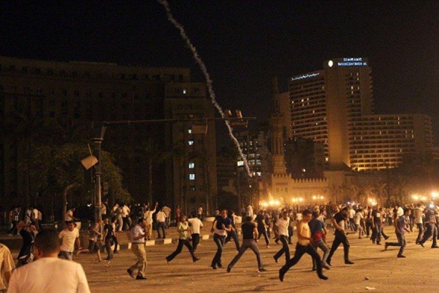 Protestuotojai bėga nuo ašarinių dujų.