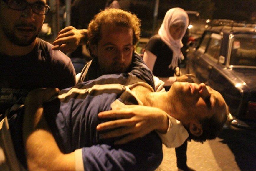 Vyrai neša sužeistą protestuotoją.