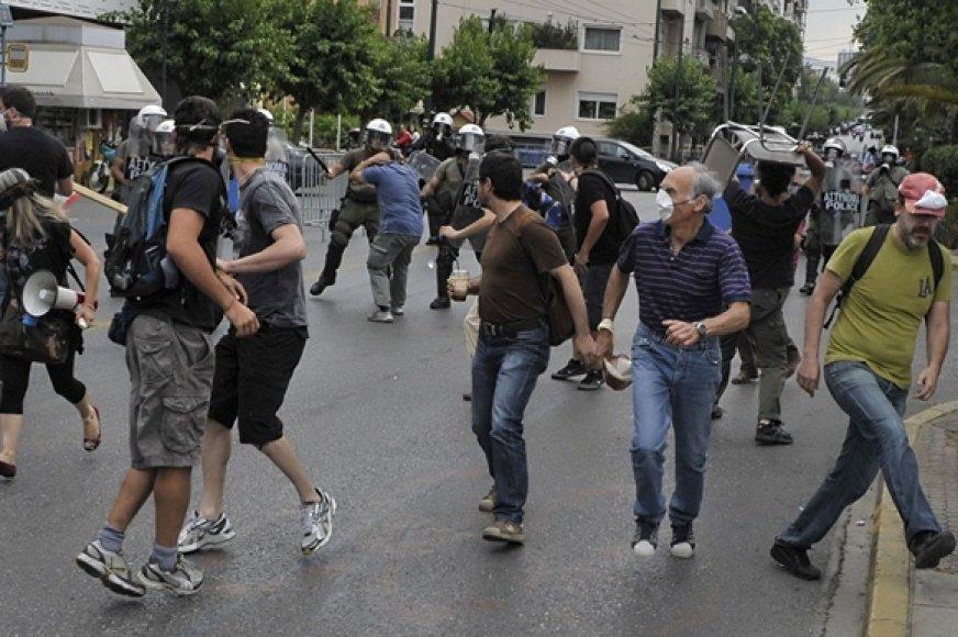 Policija vaiko kelią blokuoti bandančius protestuotojus.