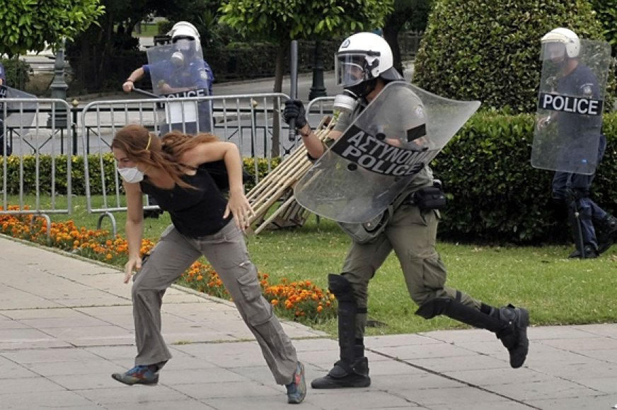Protestuotoja bėga nuo policininko.