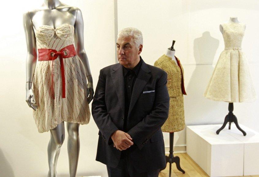 Amy Winehouse tėvas Mitchas pozuoja fotografams šalia suknelės.
