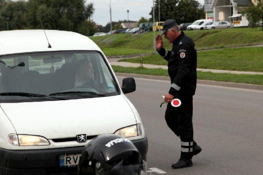 Policijos pareigūnas stabdo transporto priemonę