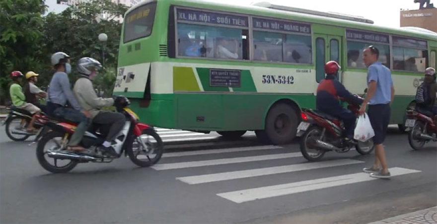 Vyras parodo gatvės perėjimo techniką Vietname
